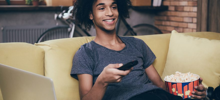 Cheerful young African man watching TV and holding remote control while sitting with bucket of popcorn on the couch at home